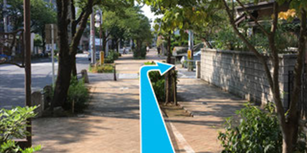木々のある歩道をまっすぐ進み、横断歩道を目印に右折します。